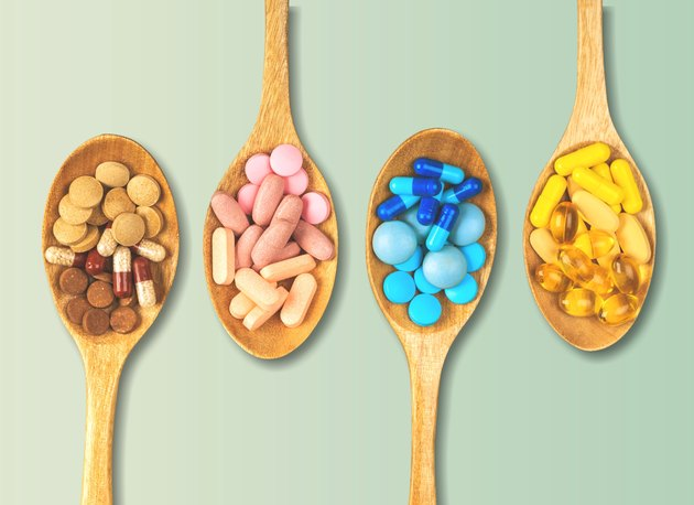 Four wooden spoons filled with multicolored supplement pills