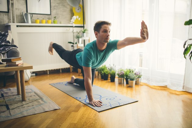 man balancing on one knee and one hand practicing yoga on mat at home