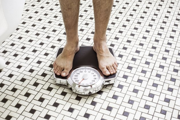 Adult man who takes Metformin standing on bathroom scales.
