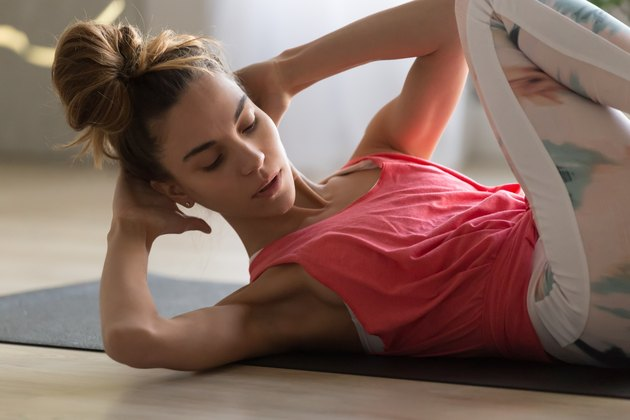 woman doing crisscross crunches in amrap workout at home
