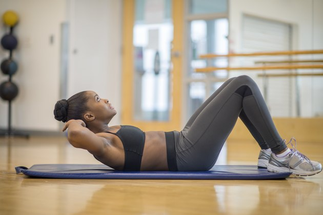 Woman doing crunches and other ab exercises in the gym