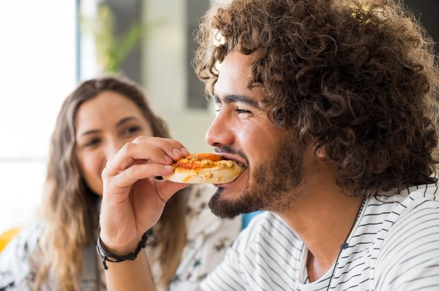Man eating pizza to show off