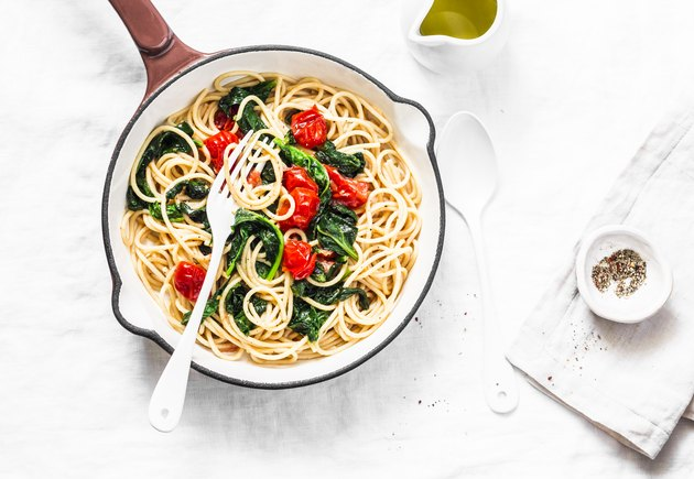 Whole grain spaghetti pasta with cherry tomatoes and spinach sauce in a cast iron pan on a white background, top view. Copy space, healthy diet food concept