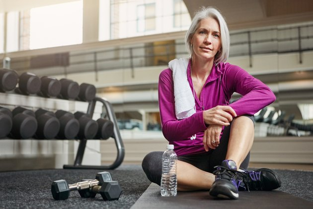 A woman over 60 losing weight by exercising at the gym