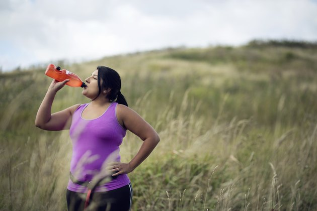 Female jogger drinking diet supplements like Plexus from bottle