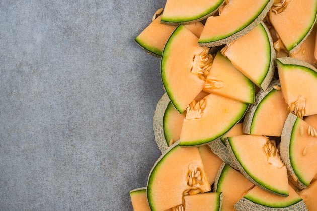 Cantaloupe melon slices, food border background