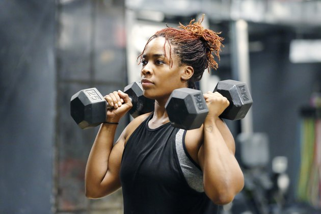 Fit, young African American woman working out with hand weights in a fitness gym.