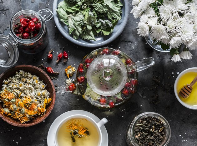 Herbal tea with currant, mint, raspberry leaves, chamomile and calendula flowers, rose hips, teapot on a dark background, top view. Flat lay
