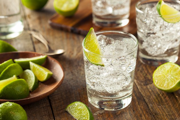 A glass of clear tequila on the rocks with lime on a wooden table