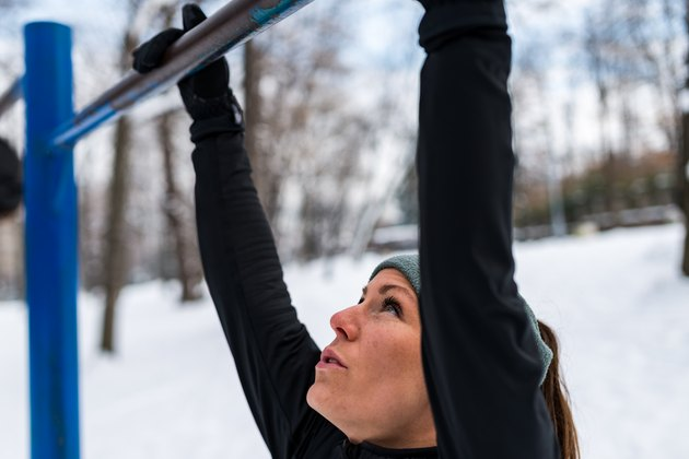 Close-Up Of Woman Holding From Monkey Bars In Public Park During Winter