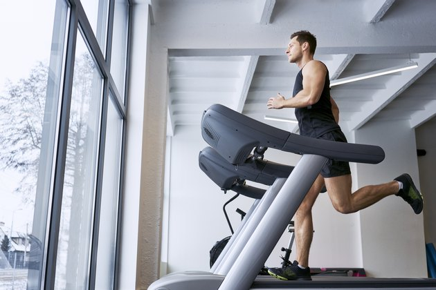 Man doing treadmill workout while looking out large window