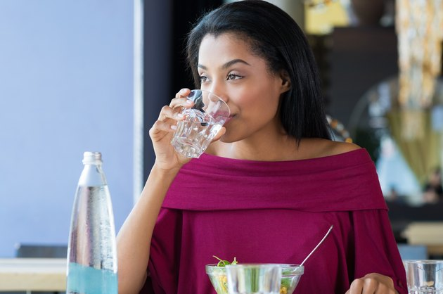 A woman sitting at a table and drinking water before eating lunch