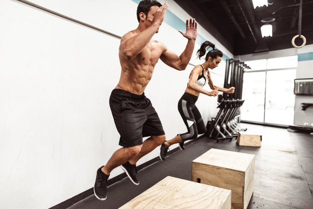 Man and woman doing box jumps at the gym as part of a HIIT workout.