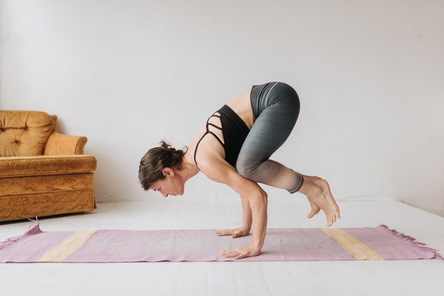 Woman doing crow pose while practicing yoga in studio