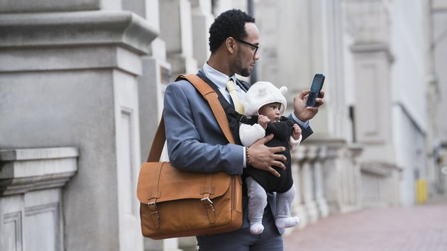 Black businessman with son in baby carrier texting on cellphone