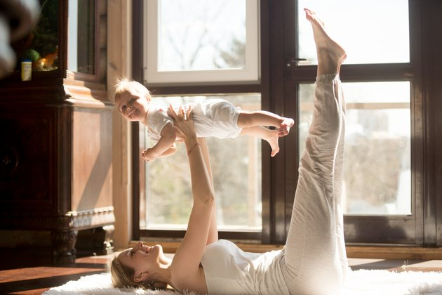 Young yogi mother exercising at home, holding her baby daughter