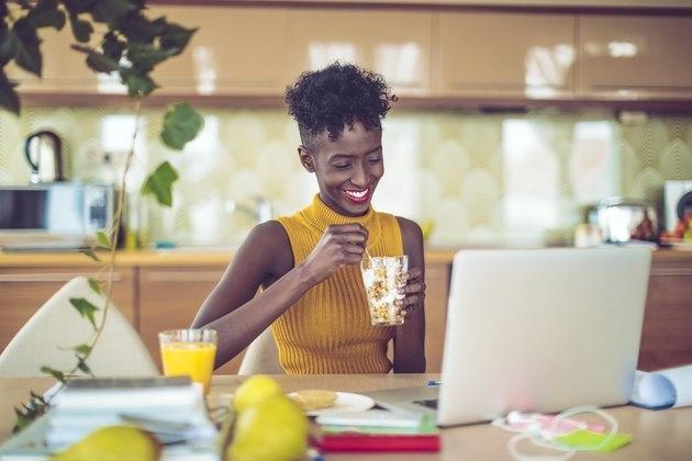 Woman eating healthy breakfast in office