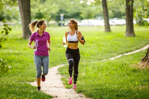 Young women running together in the park