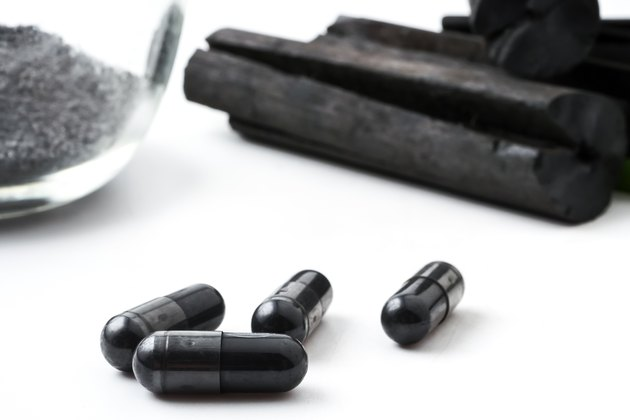 Charcoal (activated carbon) in capsules on white background
