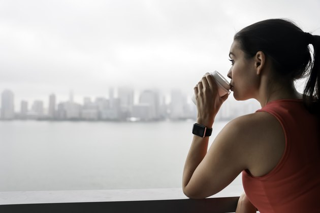 A young woman drinking coffee before a workout