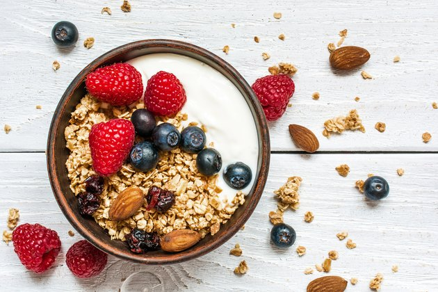 bowl of oat granola with yogurt, fresh raspberries, blueberries