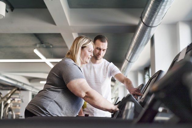 Attractive overweight woman with her personal trainer running on treadmill in modern gym.