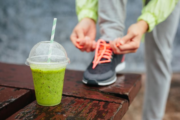 Sports nutrition smoothie next to person tying shoes before workout