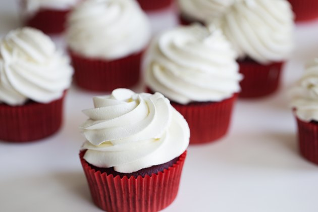 cupcakes topped with swirl of sweet vanilla frosting. Red velvet cupcakes