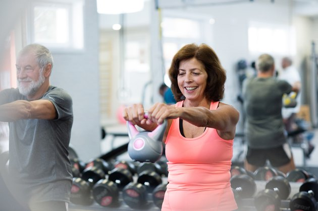 Senior couple in gym working out using kettlebells