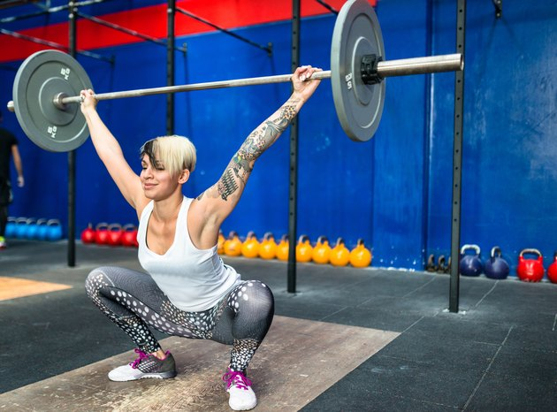 woman doing a strong training with the barbell