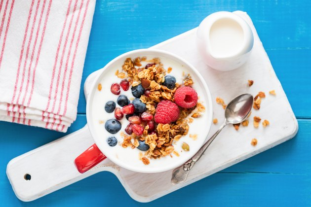 Yogurt with pomegranate seeds, fruits and breakfast cereals