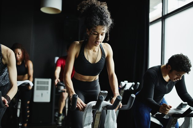 Woman riding out of saddle during indoor cycling class in fitness studio
