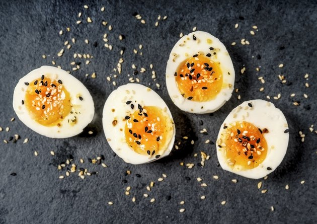Halved hard-boiled eggs on black background as part of a keto diet breakfast
