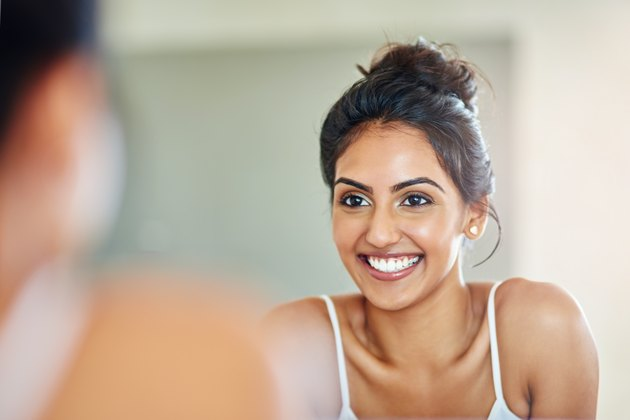 Smiling woman looking at her reflection in the bathroom mirror