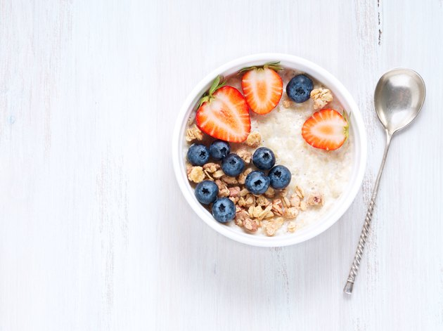 Oatmeal porridge with strawberry, blueberry, granola on white wooden background. Healthy breakfast. Top view, copy space