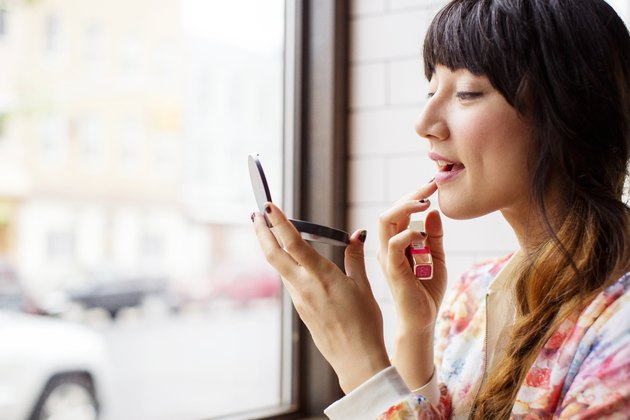 Woman applying lipstick while sitting in bar