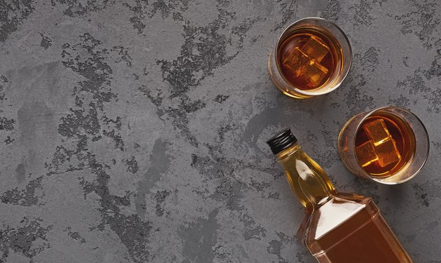 Two glasses of whiskey and bottle aside on marble background