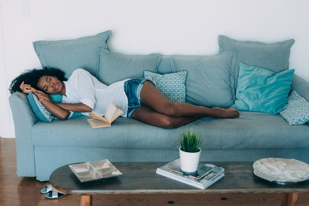 A young black woman taking a nap on a blue sofa