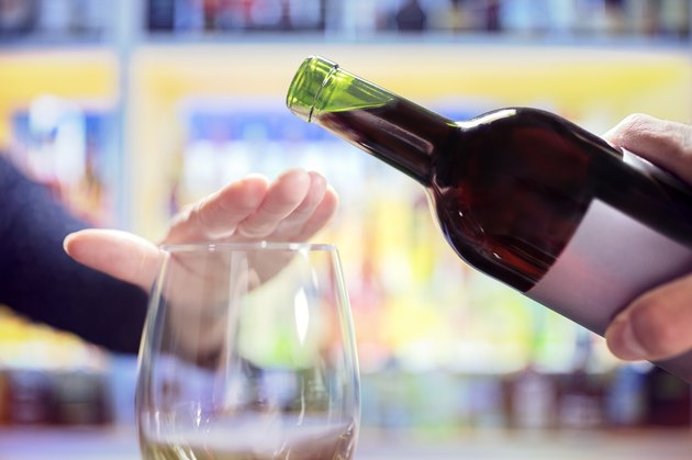 Woman rejecting more alcohol from wine bottle in bar