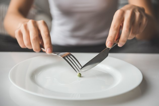 A woman cutting a pea with a knife and fork; diet concept