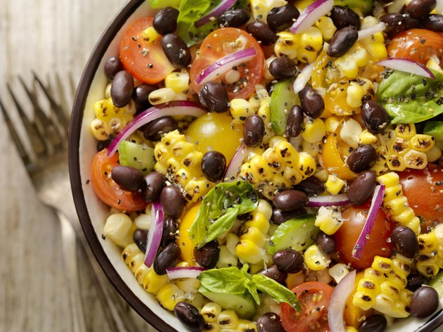 Top view of a grilled corn and black bean salad with tomatoes and onions