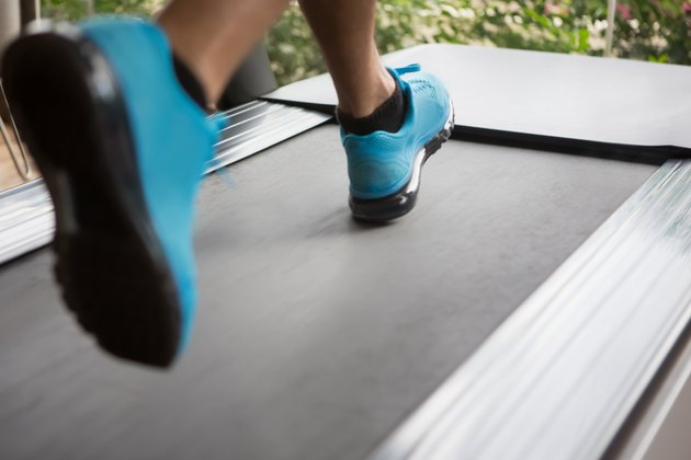 Runner's blue sneakers on treadmill doing cardio for weight loss