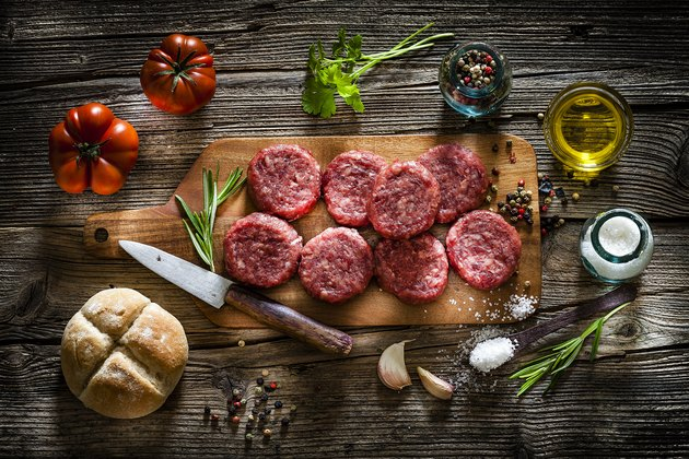Raw hamburger patties with ingredients shot from above