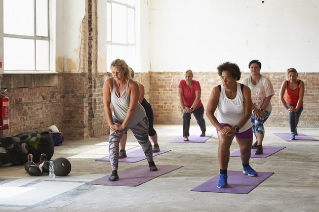 A female fitness trainer leading a workout class for middle-aged women at the gym