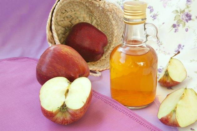 Apple cider vinegar in a bottle with apples on pink background