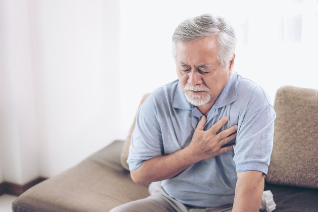 A senior Asian male holding his chest and suffering from stabbing pain when breathing