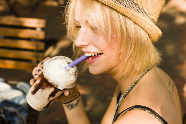 Young woman drinking gluten frappe with a straw