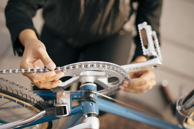 Midsection of businesswoman repairing bicycle in city