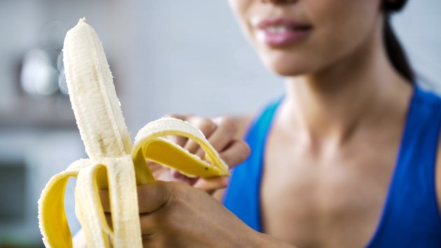 Sports woman peeling sweet banana and diabetes for snack, hungry after active workout in gym