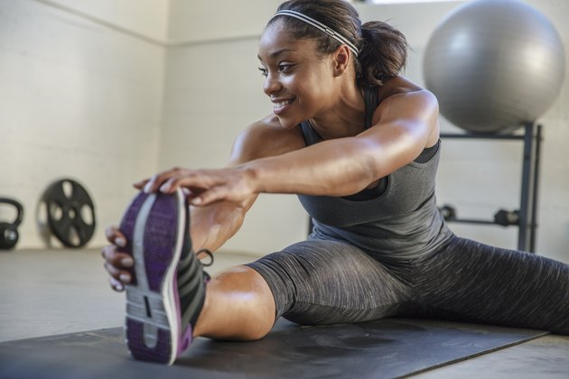 Smiling athlete stretching legs on exercise mat in health club
